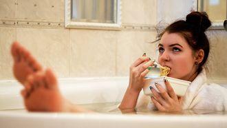 Vrouw die alleen thuis is en in haar badjas in bad zit met een bord pasta