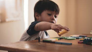 Jongetje dat met blokkenspeelt en misschien autisme heeft