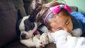 Meisje dat met hond op de bank ligt te slapen