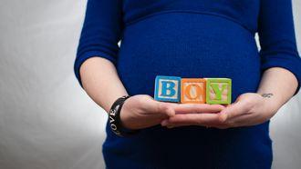 Zwangere vrouw die het geslacht van de baby laat zien
