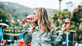 Vrouw die twee glazen wijn drinkt