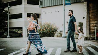 vader en moeder lopen met kinderen over zebrapad