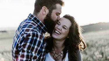 Gelukkig stelletje dat elkaar een kus geeft en sinds hun relatie wat dikker is geworden