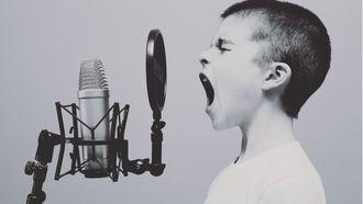 Jongetje die in een microfoon kinderliedjes zingt
