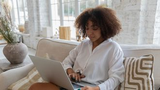 Vrouw die op de bank een sollicitatiebrief schrijft