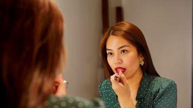 vrouw doet een rode kleur lippenstift op
