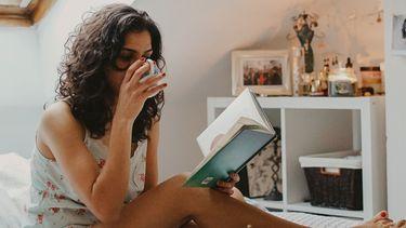 vrouw zit ontspannen op bed en leest een boek