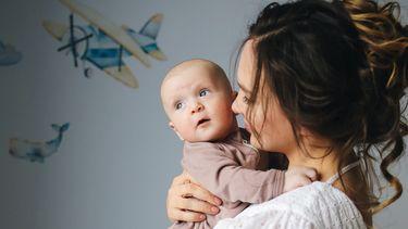 Moeder en baby in de kinderkamer met een leuk behang