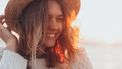 Vrouw houdt lachend haar hoed vast en haar hormonen zijn in balans