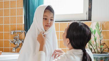 haren wassen / kind met handdoek kijkt naar moeder