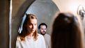 Vrouw die in de spiegel kijkt en man die haar manipuleert via gaslighting