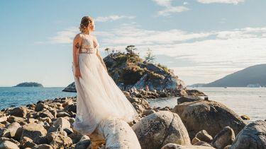 Vrouw in bruidsjurk op de rotsen voor een eiland