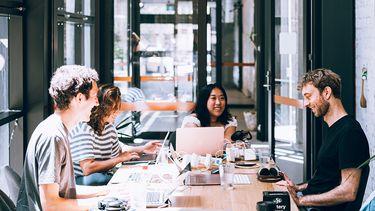 Een groepje collega's aan tafel, waar altijd wel een irritante collega tussen zit