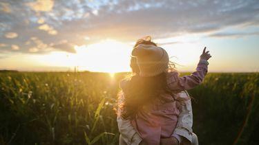 Moeder die haar dochter iets leert midden in een maisveld