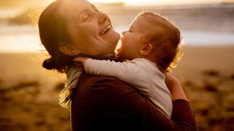 Moeder die haar baby knuffelt op het strand