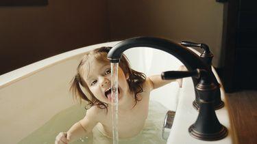 kind steekt haar tong uit om water op te likken