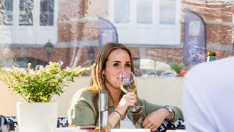 meisje zit in een restaurant en drinkt een glas wijn