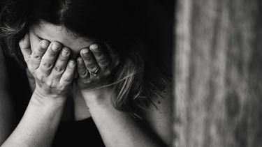 Vrouw huilt met handen voor gezicht omdat ze liefdesverdriet heeft