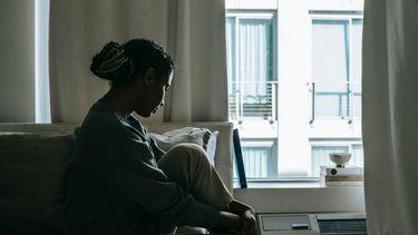 Vrouw die depressief uit het raam kijkt