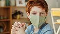 Kind met mondkapje dat vragen heeft over corona