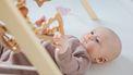 Baby die ligt te spelen in een babygym