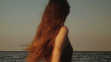 vrouw staat bij de zee