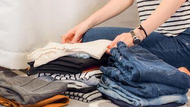 vrouw ruimt en vouwt haar kleding op
