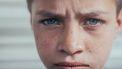 Jongetje dat verdrietig in de camera kijkt omdat hij gepest is