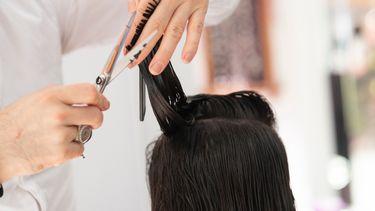 vrouw laat haar haar knippen