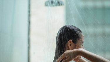 Vrouw die onder de douche staat en haar haar wast