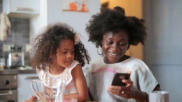 Vrouw die haar dochter op schoot heeft en op haar telefoon kijkt