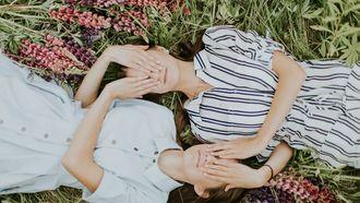 twee zussen liggen in het gras