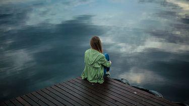Vrouw die eenzaam over het water kijkt omdat ze moederdag zonder moeder moet vieren