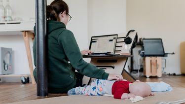 werken na verlof / moeder werkt met baby op de grond