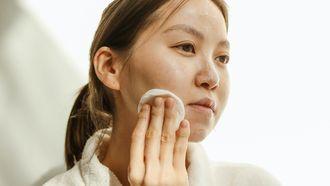 vrouw verzorgt haar huid met een watje