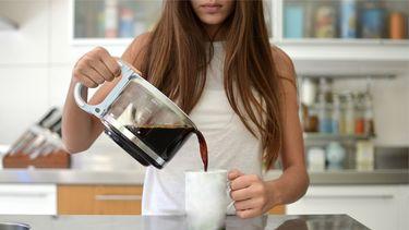 Vrouw die een kopje koffie zet na het gourmetten om de gourmetlucht te verwijderen