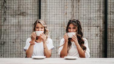 twee vriendinnen drinken een kop koffie samen