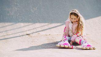 Meisje dat met skates en roze kleren aan op de grond zit