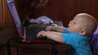 Baby die op de laptop zit