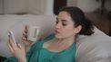 Vrouw die op haar telefoon leest dat ze voor haar veertigste overgangsklachten van de perimenopauze kan aanpakken