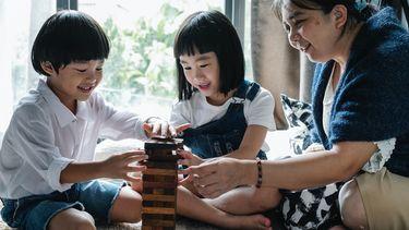 Moeder die een spelletje speelt met haar kinderen en hen laat winnen