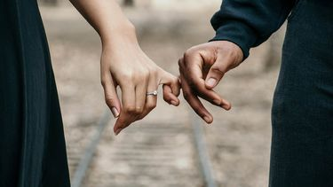 Vrouw en mannen hand houden elkaars pink vast. Met een liefdesformule de lengte van je relatie bepalen