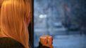 Moeder die uit het raam kijkt met een beker in haar hand