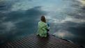 Vrouw die op een stijger naar het water kijkt en zich eenzaam en gebroken voelt