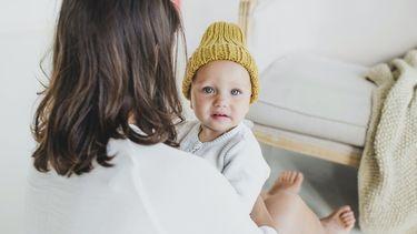 Moeder die een baby vasthoudt die een gele muts op heeft en een Hollandse jongensnaam heeft gekregen