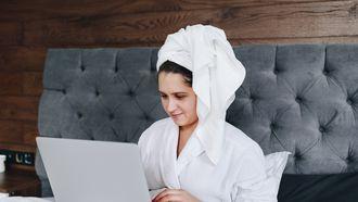 Vrouw zit met handdoek te achter haar laptop en heeft het thuiswerken onder de knie