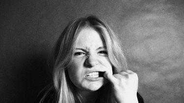 Vrouw die met haar vinger haar stroeve tanden probeert schoon te maken na het eten van spinazie