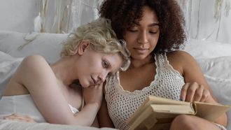 Stelletje in gelukkige relatie dat samen op bed en boek leest