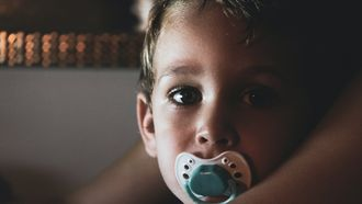 Jongetje met een speen die in de camera kijkt
