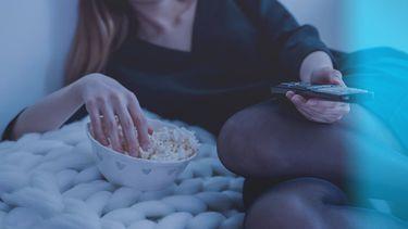 eten / vrouw eet popcorn terwijl ze tv kijkt